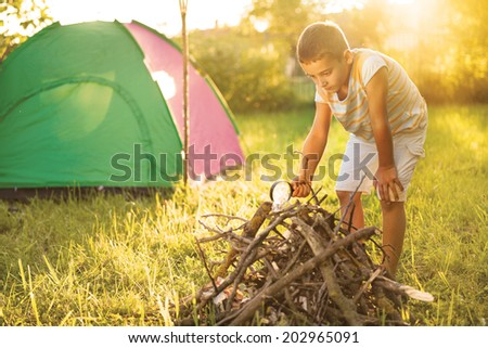 child on a camping trip using a magnifying glass to light a fire - stock photo