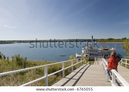 Child on a dock with a moored steamboat. Heritage Park HIstorical Village, Calgary, Canada - stock photo