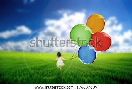 Child on a green meadow playing with colored balloons  - stock photo