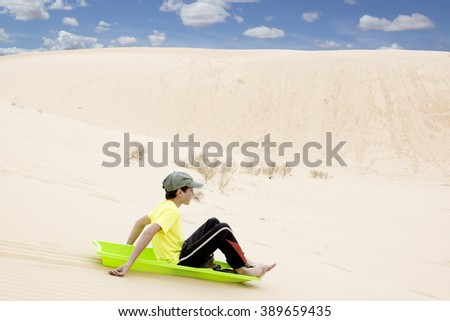 Child on a sled pulls off the sandy mountains.  Monahans Sandhills State Park, Texas, USA - stock photo