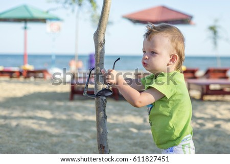 Child on a sunny day on the beach with glasses in hand