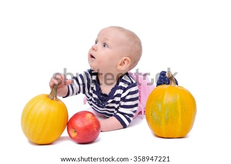 child on a white background with pumpkins and apples/charming child with pumpkins and apples on a white background - stock photo