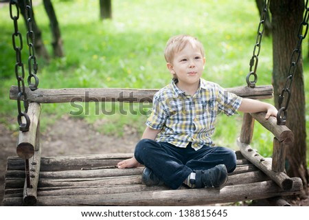 child on a wooden swing - stock photo