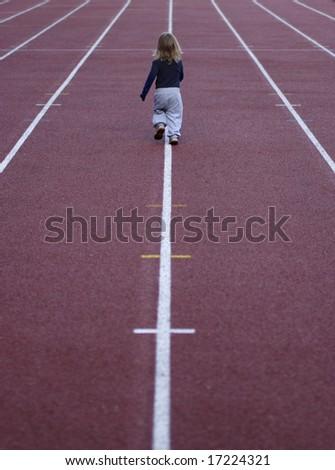 child on athletic stadium running track - stock photo