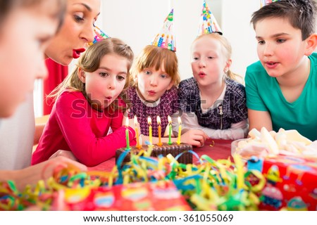 Child on birthday party blowing candles on cake being helped by friends and the mother - stock photo
