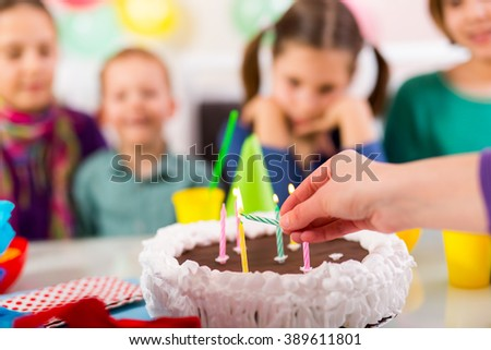Child on birthday party preparing blowing candles on cake - stock photo