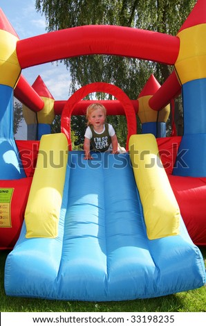 child on bouncy castle. inflatable blow-up toy for kid in garden - stock photo