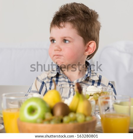 Child on breakfast - looking capricious while sitting at home near table - stock photo