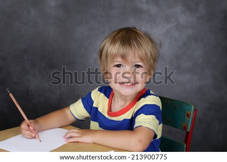"Child on chair in classroom with a blank page, ""back to school"" theme,  - stock photo"