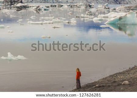 Child on coast of Jokulsarlon glacier lagoon. Iceland. - stock photo