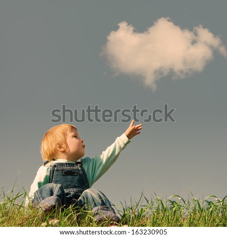 child on green grass under blue sky - stock photo