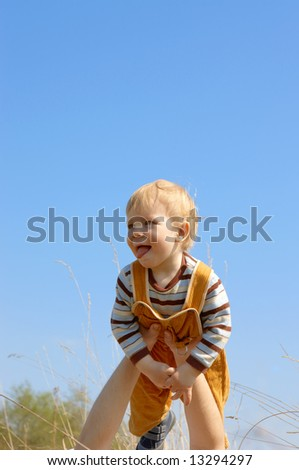 child on hands on a background of the sky - stock photo