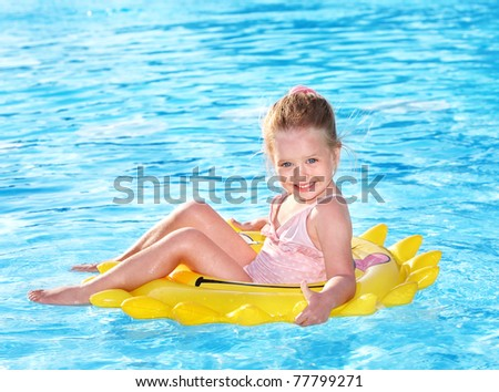 Child  on inflatable ring in swimming pool. - stock photo
