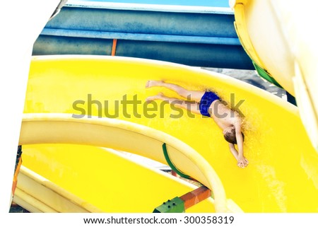 Child on summer vacation in water park taking a fast ride. Active summer concept.  - stock photo