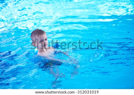 child on swimming pool learning to swim w