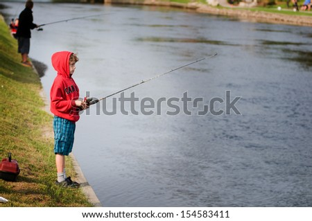 child on the bank of a river fishing - stock photo