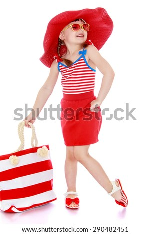 Child on the beach in a red bathing suit with a bag - isolated on white background - stock photo