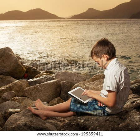Child on the beach with tablet computer - stock photo