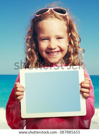 Child on the beach with tablet computer. Little happy girl showing screen digital pc - stock photo