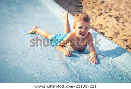Child on water slide at aquapark during summer holiday - stock photo