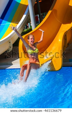 Child on water slide at aquapark show hands up and crying . There are some water slides with flowing water in aqua park. Summer water park holiday. Summer outdoor.