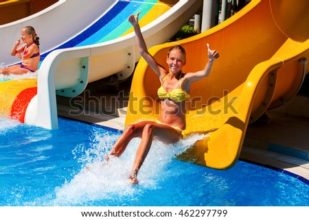 Child on water slide at water park show thumb up and jumb in water. .Summer outdoor water park .