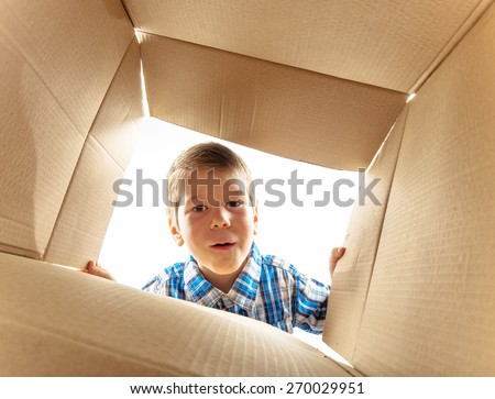 Child opening cardboard box and looking inside with surprise. - stock photo