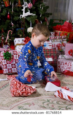 Child opening presents near the Christmas tree, Holiday has finally arrived
