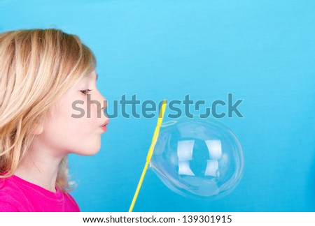 Child or girl blowing bubbles on a blue background - stock photo