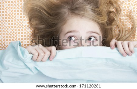 Child or teen hiding under covers in bed - stock photo