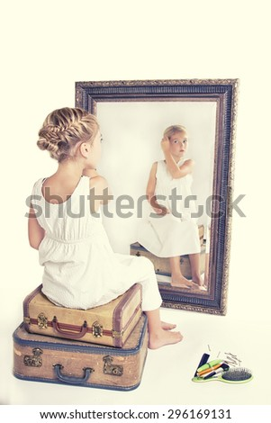 Child or young girl fixing her hair while looking at herself in a mirror, sitting on vintage luggage, with a fish tail braid in her hair. Vintage or retro filter applied. - stock photo