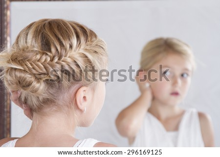 Child or young girl fixing her hair while looking in the mirror. - stock photo
