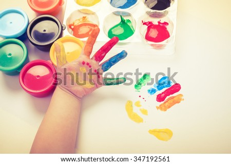 Child paint her palm with smiling face various colors using multicolored drawing tools. Studio shot. Cream tone. - stock photo