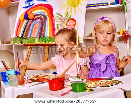 Child painting at easel. - stock photo