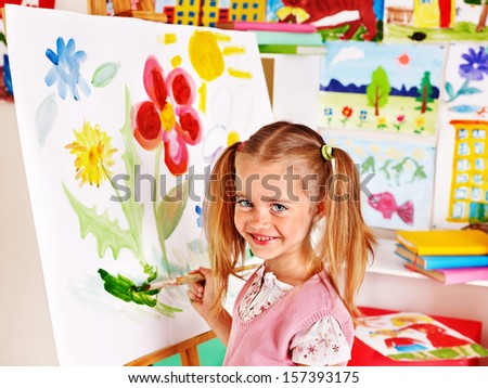 Child painting at easel in art class. - stock photo