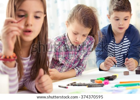 Child painting at easel in school - stock photo
