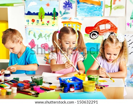 child painting at easel in school teacher help