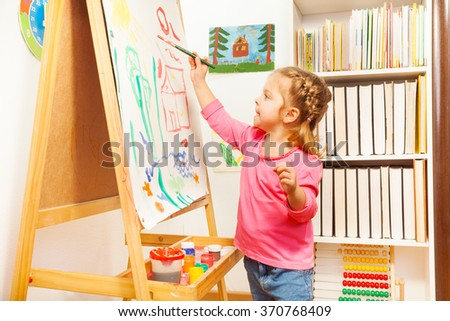 Child painting landscape picture on easel - stock photo