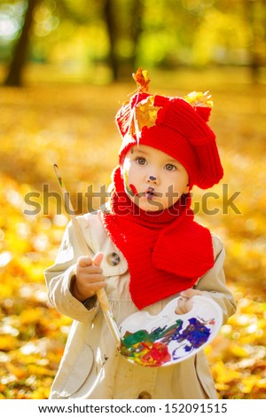 Child painting on easel in Autumn Park. Little Girl in Red Hat, Creative kids drawing development concept.