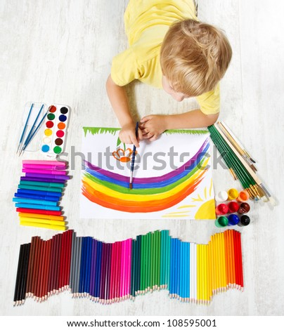 Child painting picture with brush in album using a lot of painting tools. Top view. Creativity concept.