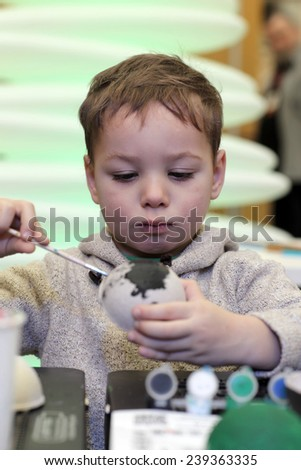 Child paints a cardboard toy in the classroom - stock photo