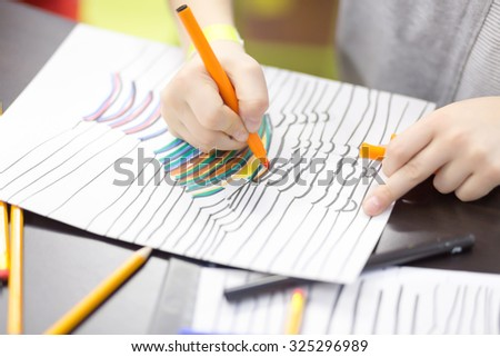 Child paints a felt pen drawing of hand - stock photo