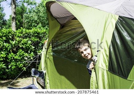 Child peeks from a green tent. Campsite - stock photo