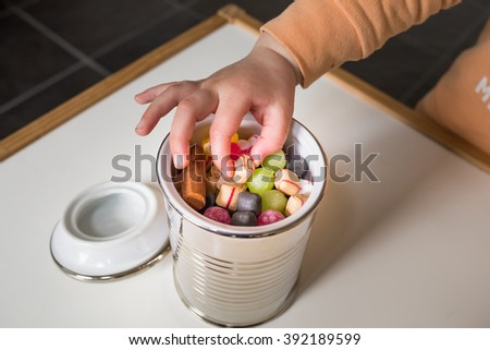 Child picks candy from a jar full of colorful candy - stock photo