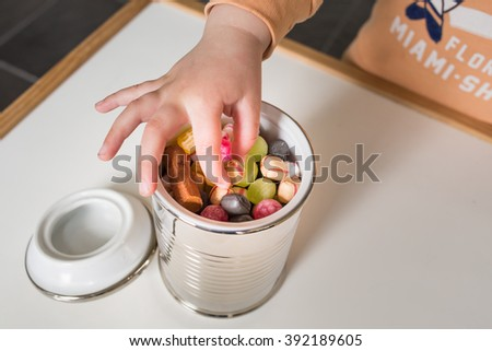 Child picks candy from a jar full of colorful candy
