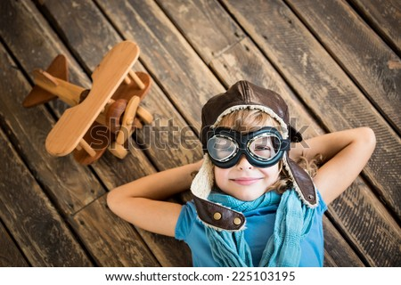 Child pilot with vintage plane toy on grunge wooden background - stock photo