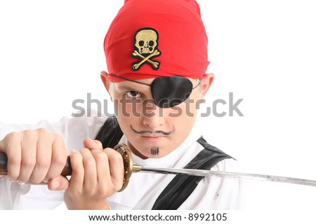 Child play acting a Pirate.  He is wearing an eye patch, wielding a sword and has a mean stare - stock photo