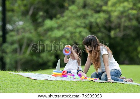 child play toy with mom in park happily. - stock photo