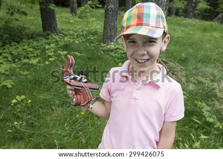 Child play with a wooden plane in the mountain. Forest - stock photo