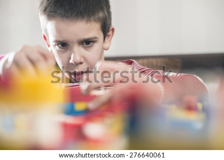 Child play with children's plastic constructor toys - stock photo